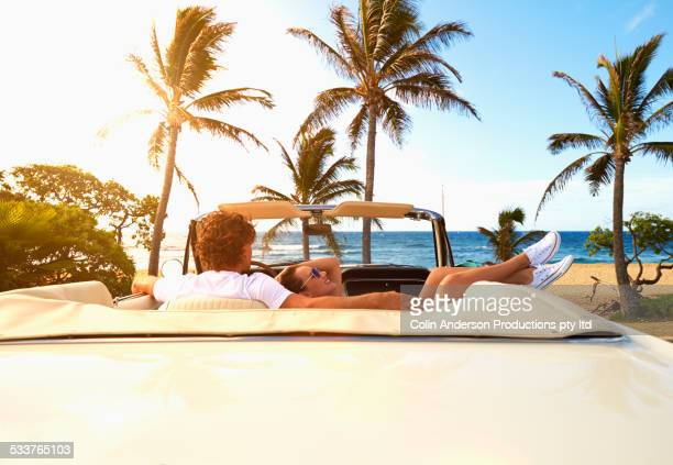 Couple relaxing in convertible on beach