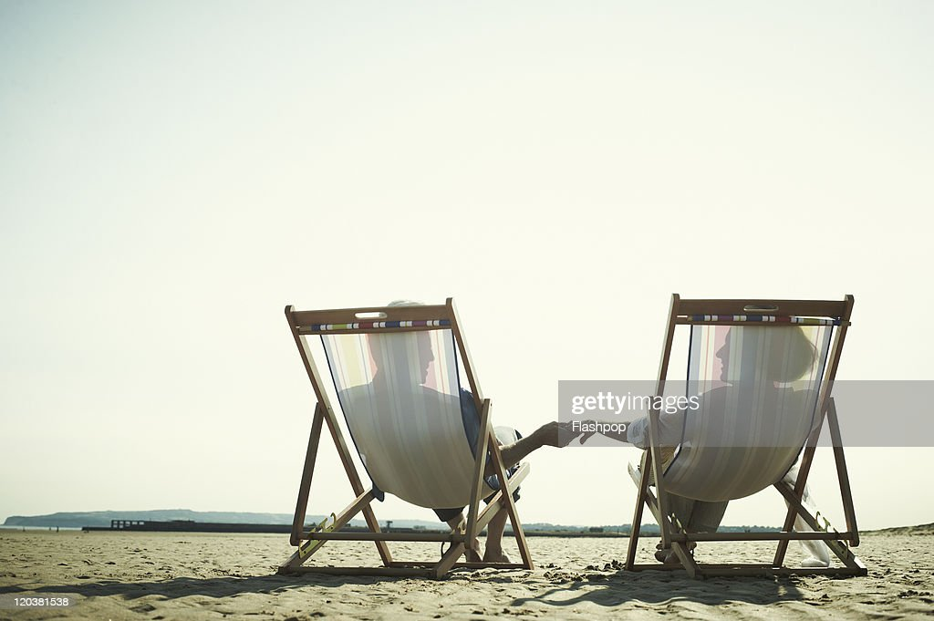 Couple relaxing in deck chairs at the beach : Stock Photo