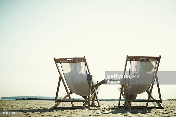 Couple relaxing in deck chairs at the beach