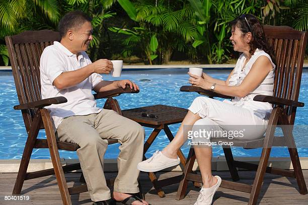 Couple relaxing in deck chairs by the pool, having tea