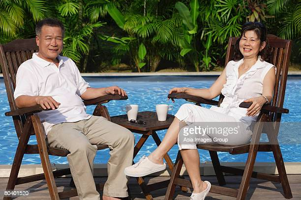 Couple relaxing in deck chairs by the pool