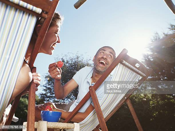 Couple relaxing in deckchairs, laughing, low angle view