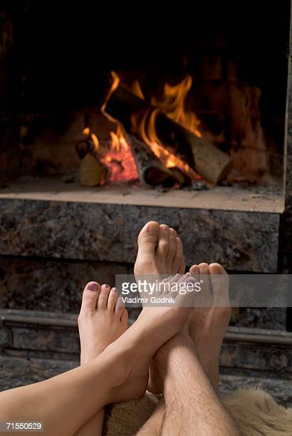 Couple relaxing in front of an open fire