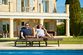 young couple relaxing on sun chairs at poolside in front of their Spanish Finca house