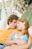 Couple relaxing in hammock on beach