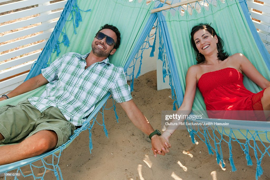 Couple relaxing in hammocks on beach : Stock Photo