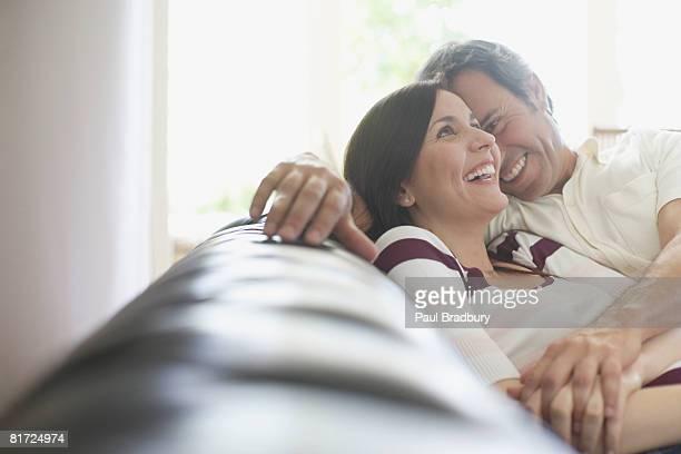Couple souriant se détendre dans la salle de séjour
