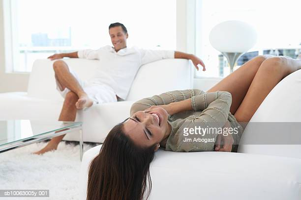 Couple relaxing in living room, woman in foreground with hair flowing down