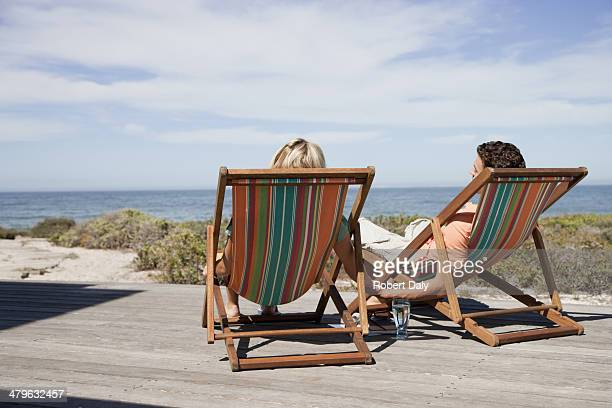 A couple relaxing in lounge chairs holding hands