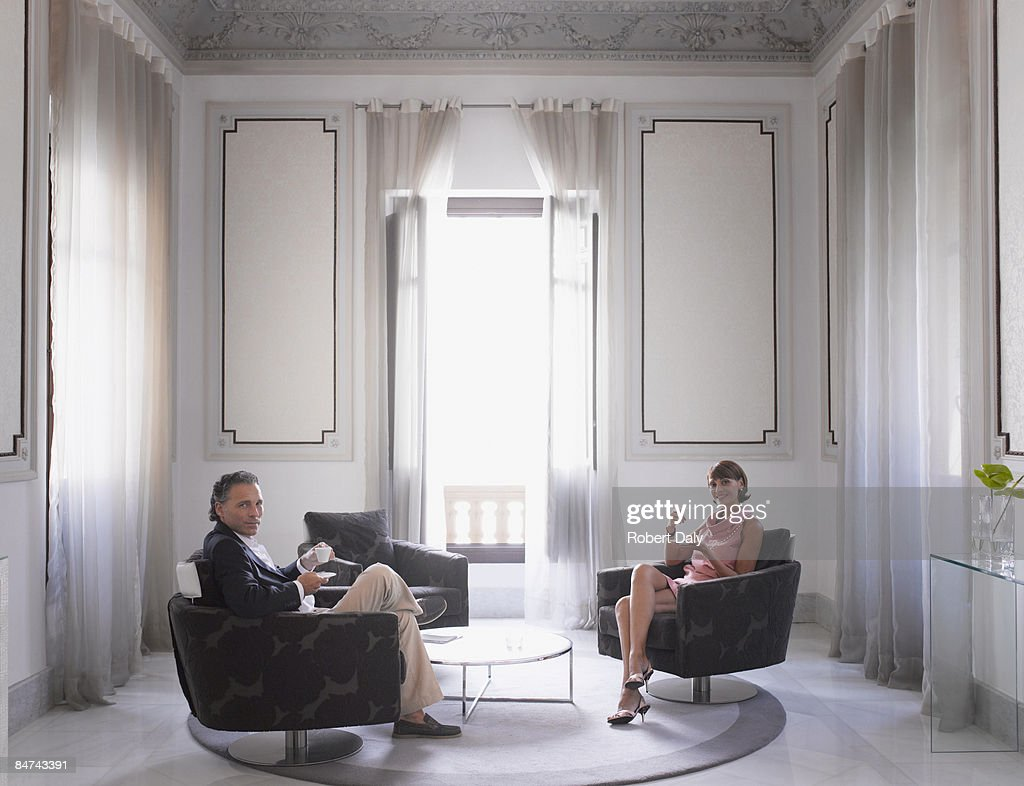 Couple relaxing in modern hotel suite : Stock Photo