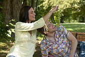 Couple relaxing in park, woman feeding man grapes, both laughing