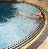 Couple relaxing in swimming pool, elevated view
