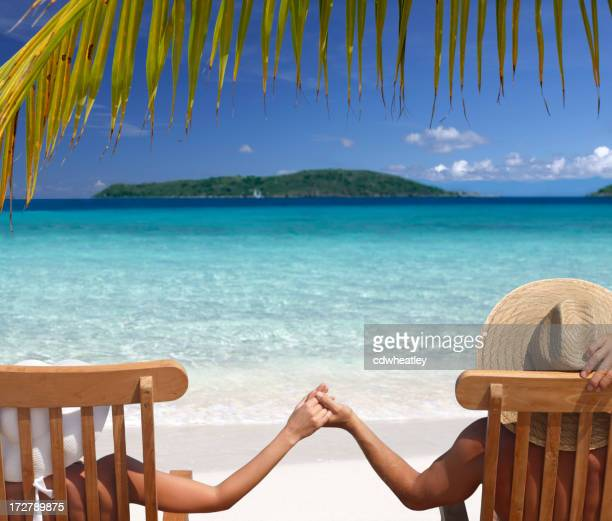 Couple relaxing in teak chairs on beautiful beach