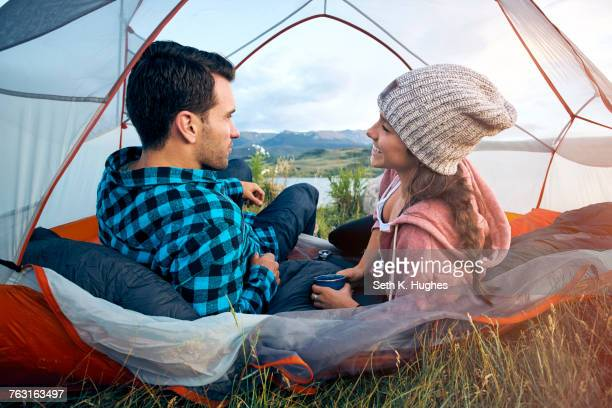 Couple relaxing in tent, rear view