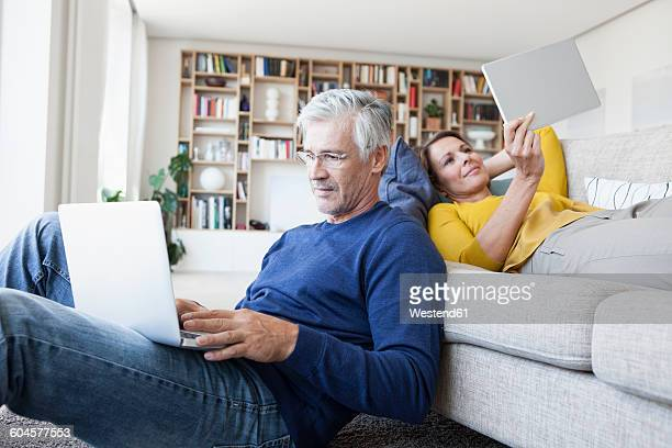 Couple relaxing in the living room with digital devices