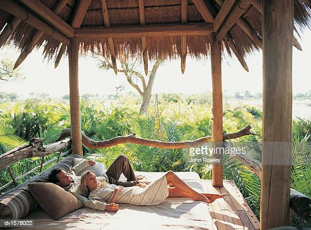 Couple Relaxing on a Bed in Their Holiday Home Overlooking the Jungle