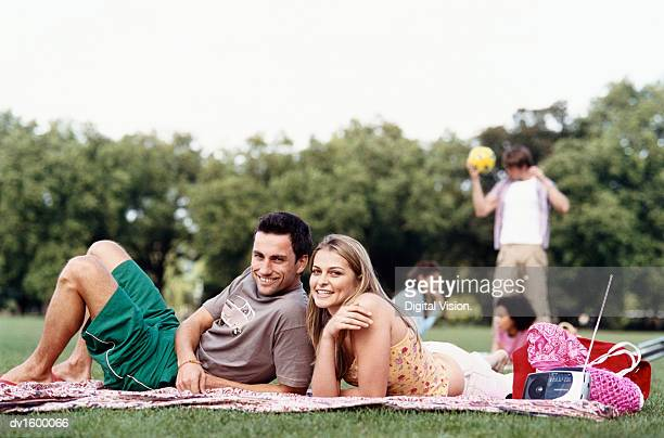 Couple Relaxing on a Blanket in a Park, with People in the Background