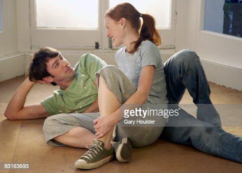 Couple relaxing on an empty floor : Stock Photo