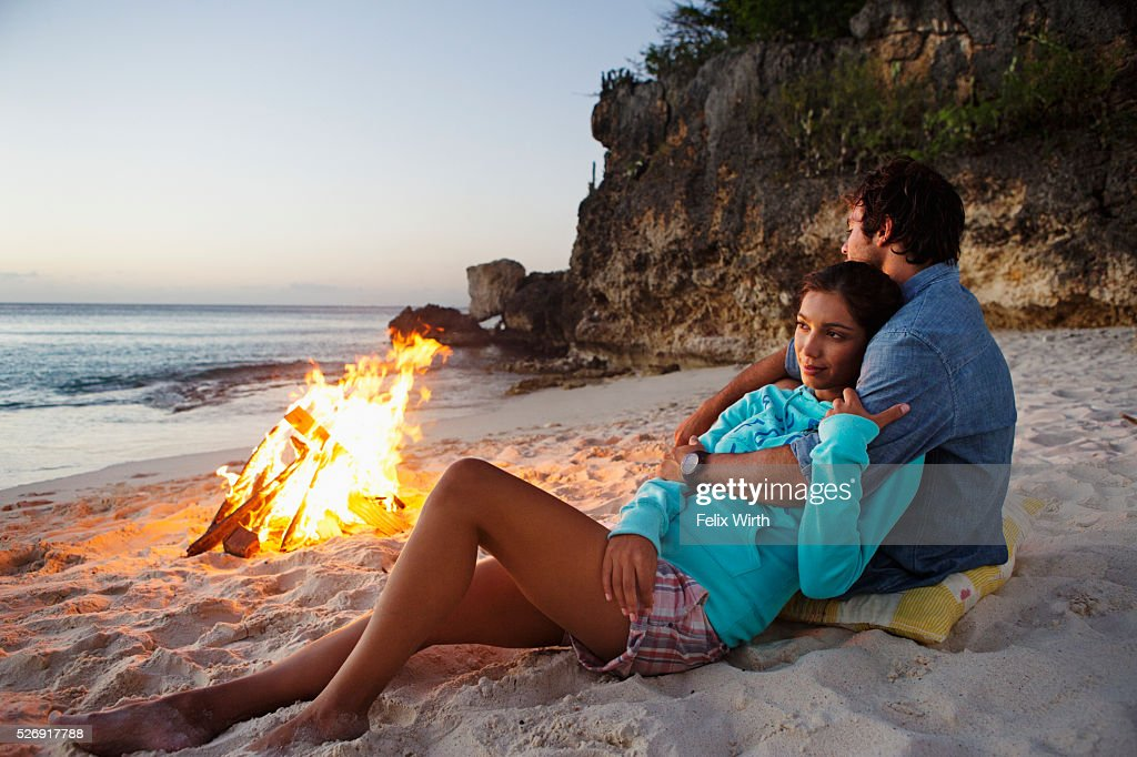 Couple relaxing on beach at campfire : Stock Photo