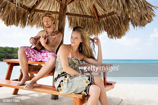 Couple relaxing on beach under sunshade : Foto de stock