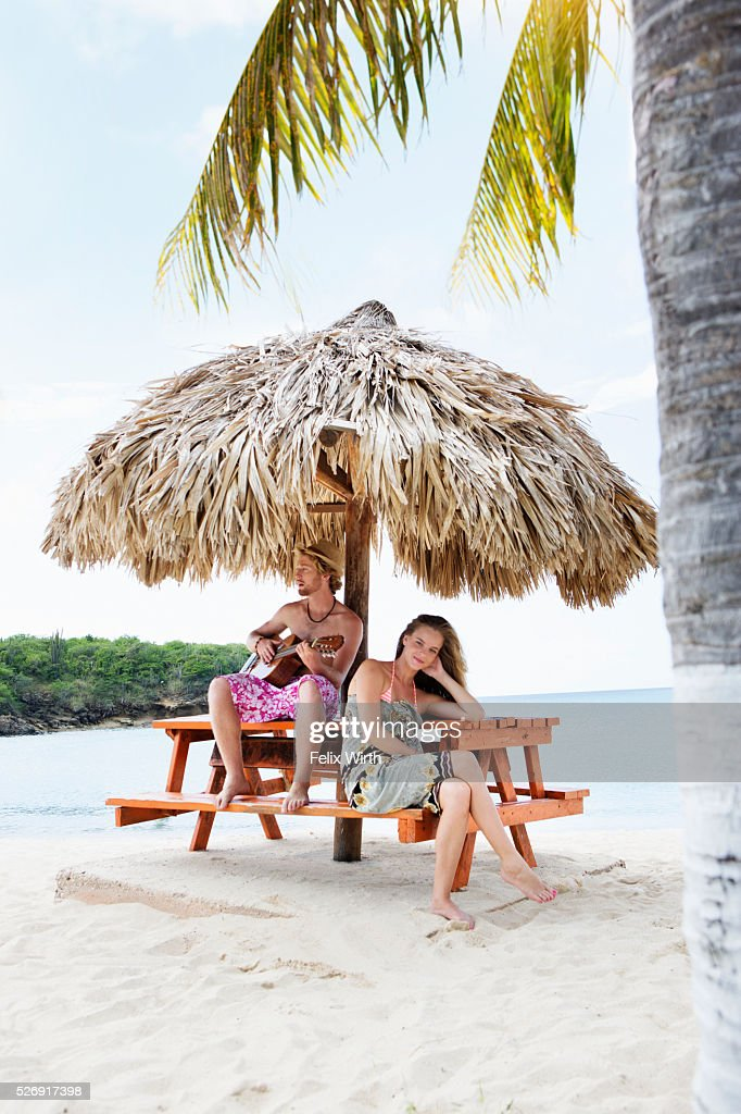 Couple relaxing on beach under sunshade : Photo