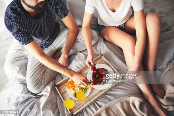 Couple relaxing on bed, eating strawberries, elevated view