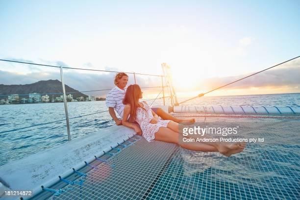 Couple relaxing on boat in ocean