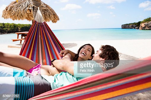 Couple relaxing on hammock on beach : Stockfoto