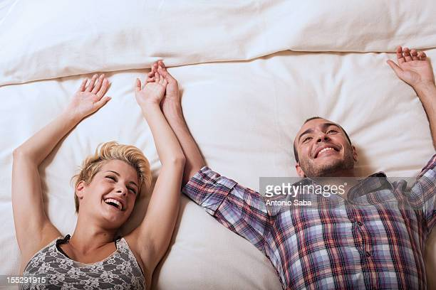 Couple relaxing on hotel room bed