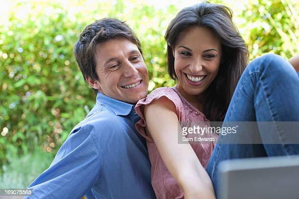 Couple relaxing on patio with laptop