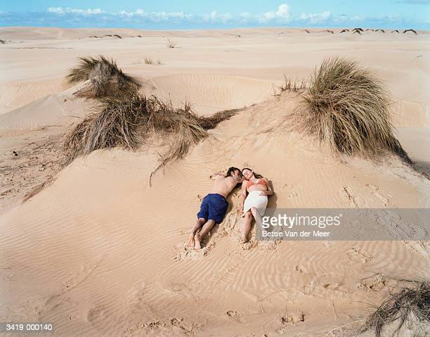 Couple Relaxing on Sand Dune