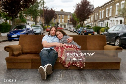 couple  relaxing on settee in the street : Stock Photo