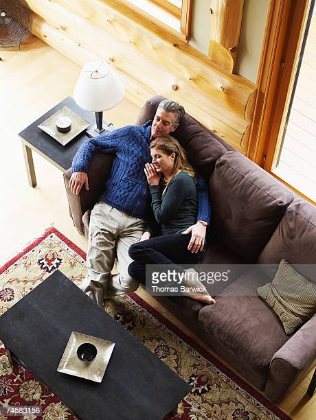 Couple relaxing on sofa, overhead view