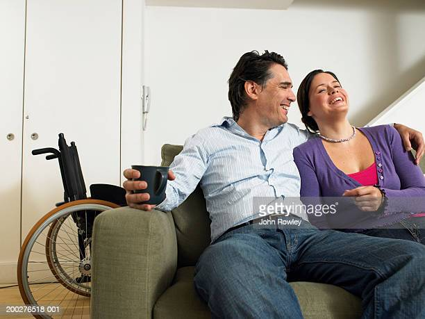 Couple relaxing on sofa, smiling, wheelchair in background