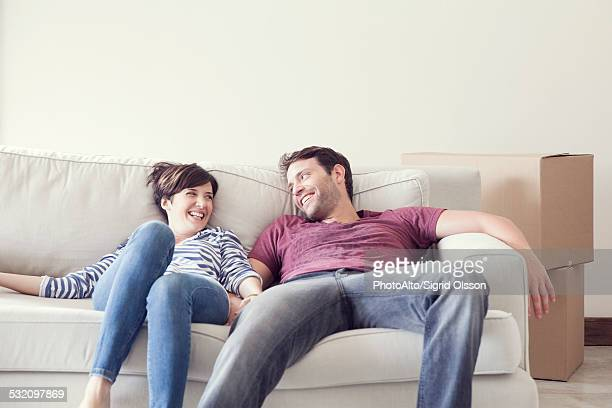 Couple relaxing on sofa while moving house