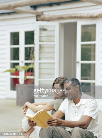 Couple relaxing on steps outside home, man holding open book : Stock-Foto
