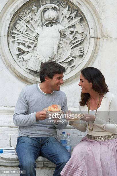 Couple relaxing on stone seat, eating slices of pizza, smiling