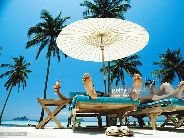Couple relaxing on sunloungers under parasol, low section