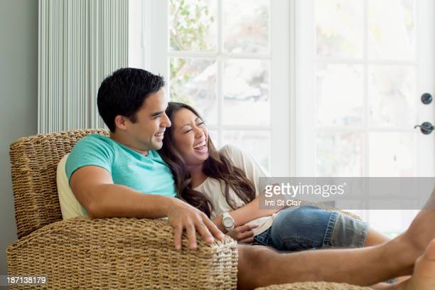Couple relaxing together in armchair