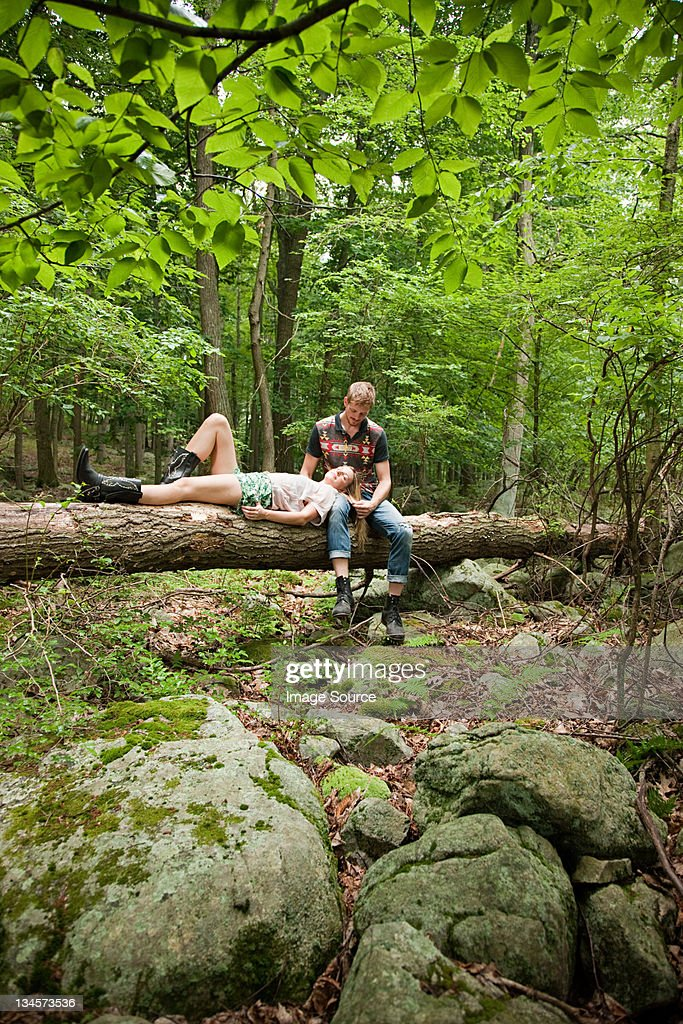 Couple relaxing together on log in forest : Stock Photo