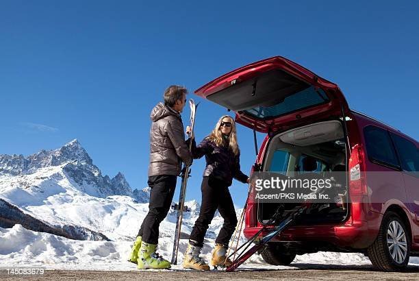 Couple remove skiis from vehicle for mtn ski day
