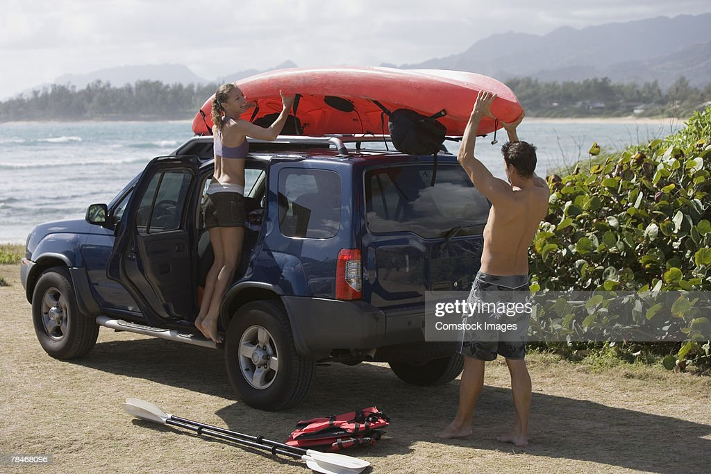 Couple removing kayak from roof of vehicle