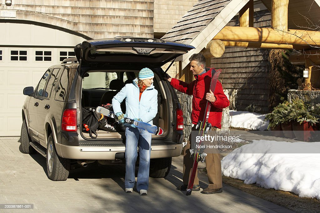 Couple removing skis from back of vehicle