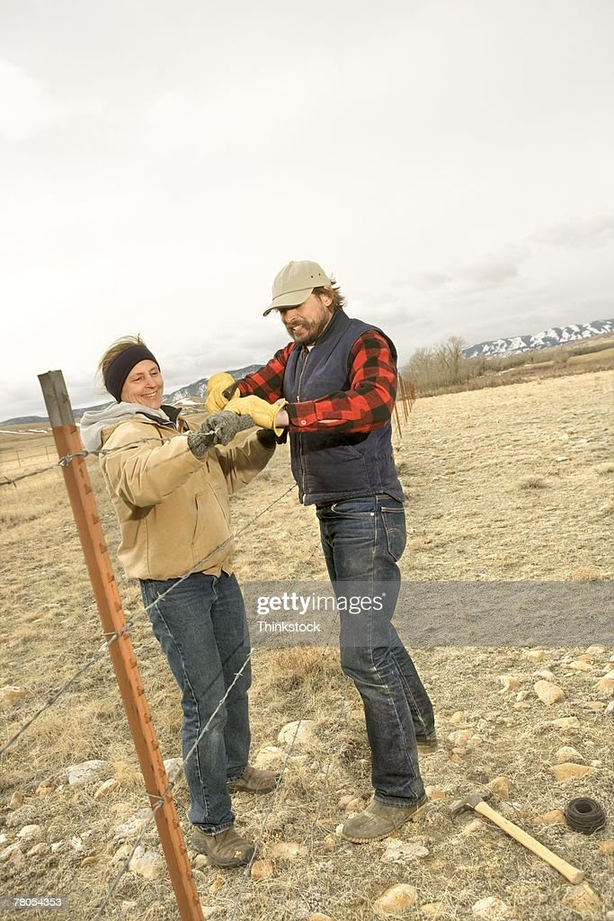 Couple repairing fence