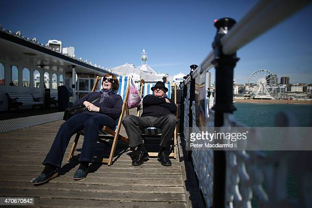 A couple rest on Brighton Pier on April 22 2015 in England Parts of the United Kingdom are experiencing warm sunny weather