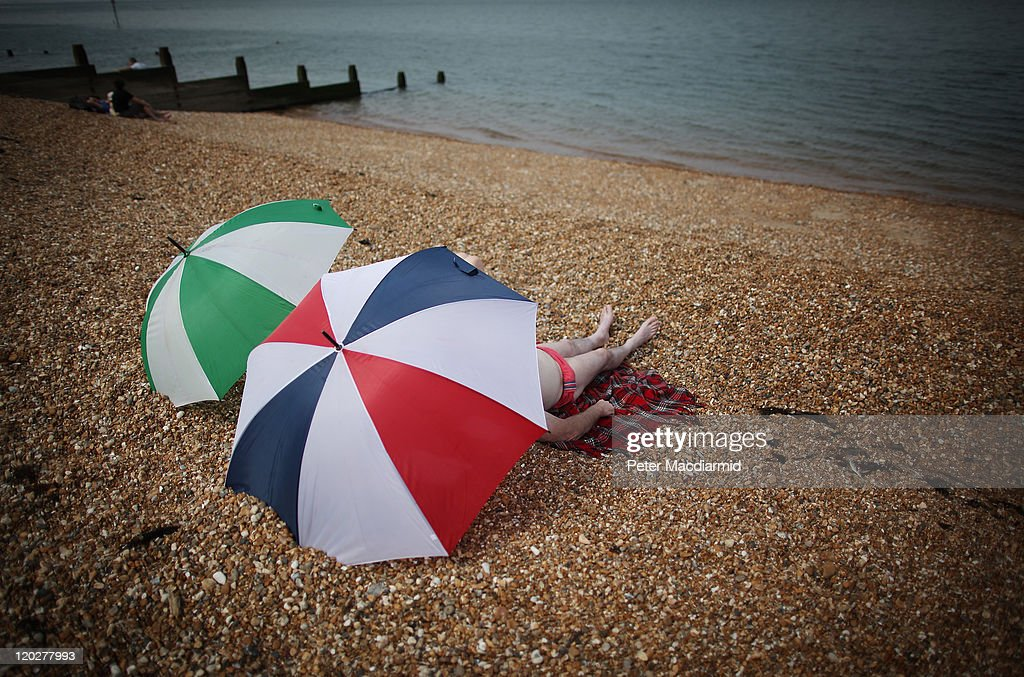 A couple rest under umbrellas on the beach on August 3, 2011 in Whitstable, England. Parts of southern England are experiencing high summer temperatures.