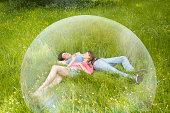 Couple resting in grass, surrounded by bubble.
