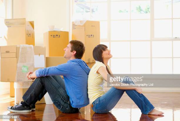 Couple resting near cardboard boxes in new home
