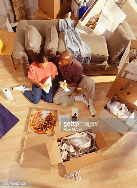 Couple resting on floor after moving into new home, elevated view