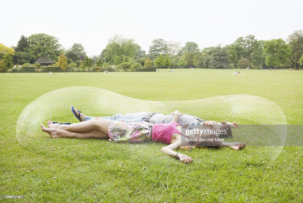 couple resting, surrounded by long bubble : Stock Photo
